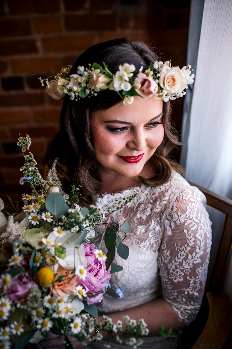 beautiful bride adorned with fresh flowers and red lipstick sitting next to the window at Curradine barns just before she gets married