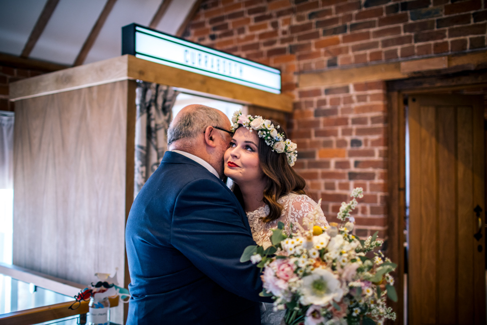 bride kissing her dad ready to walk down the aisle at the curradine barns