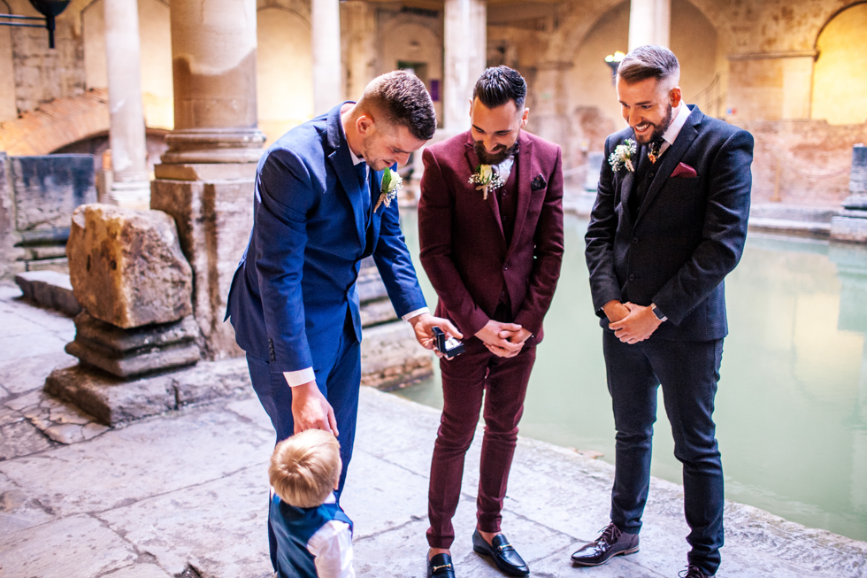 ring bearer giving groom ring next to water at Roman baths