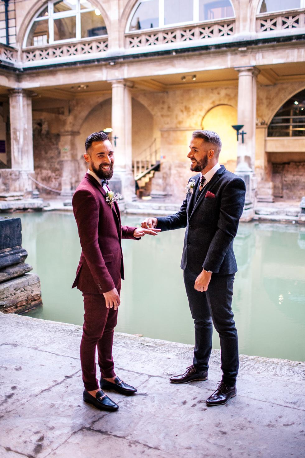 groom and groom exchanging rings at roman baths