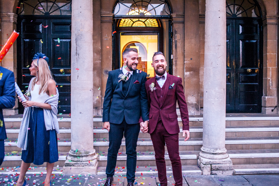 grooms laughing together after just getting married at the Roman baths