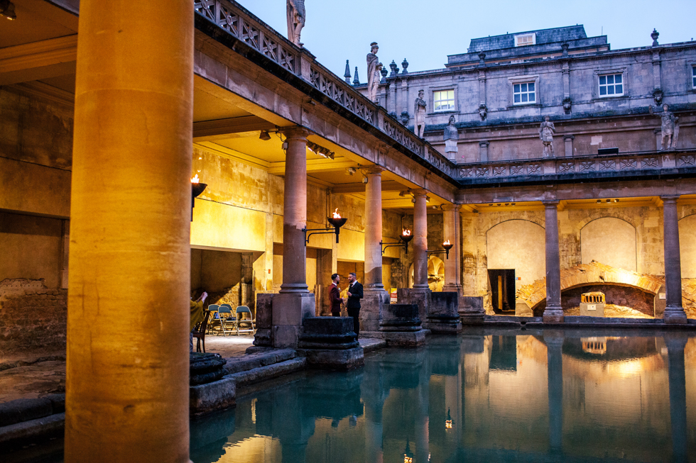 groom and groom stood together by the water for their portrait at the Roman baths