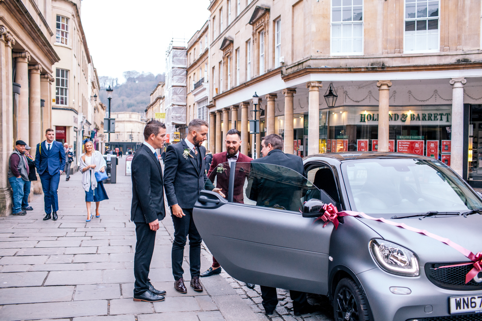 Groom and groom arriving in decorated smart car at wedding