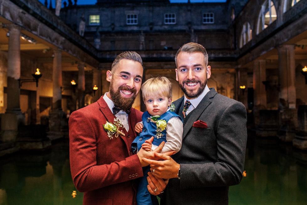 groom and groom hugging their nephew at the Roman baths