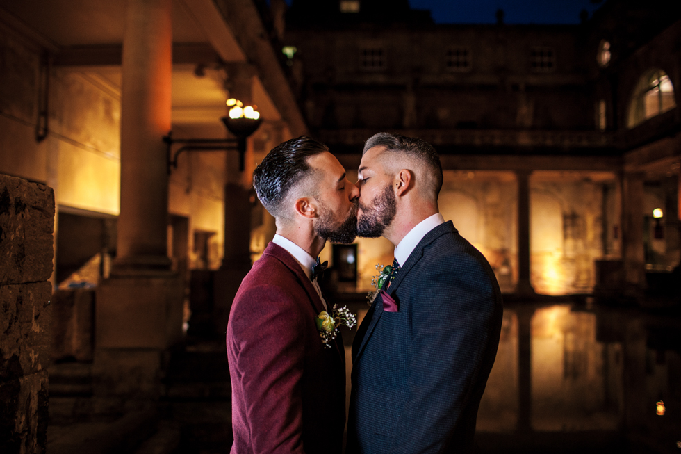 groom and groom kissing at a twilight wedding at the Roman baths