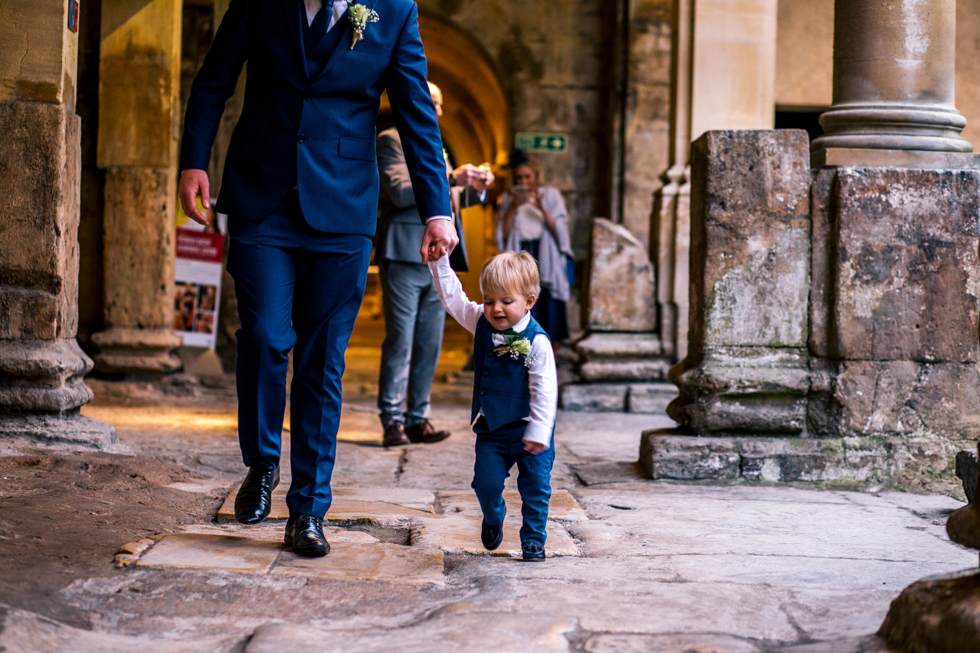 18 month toddler walking into ceremony room as ring bearer at Roman baths