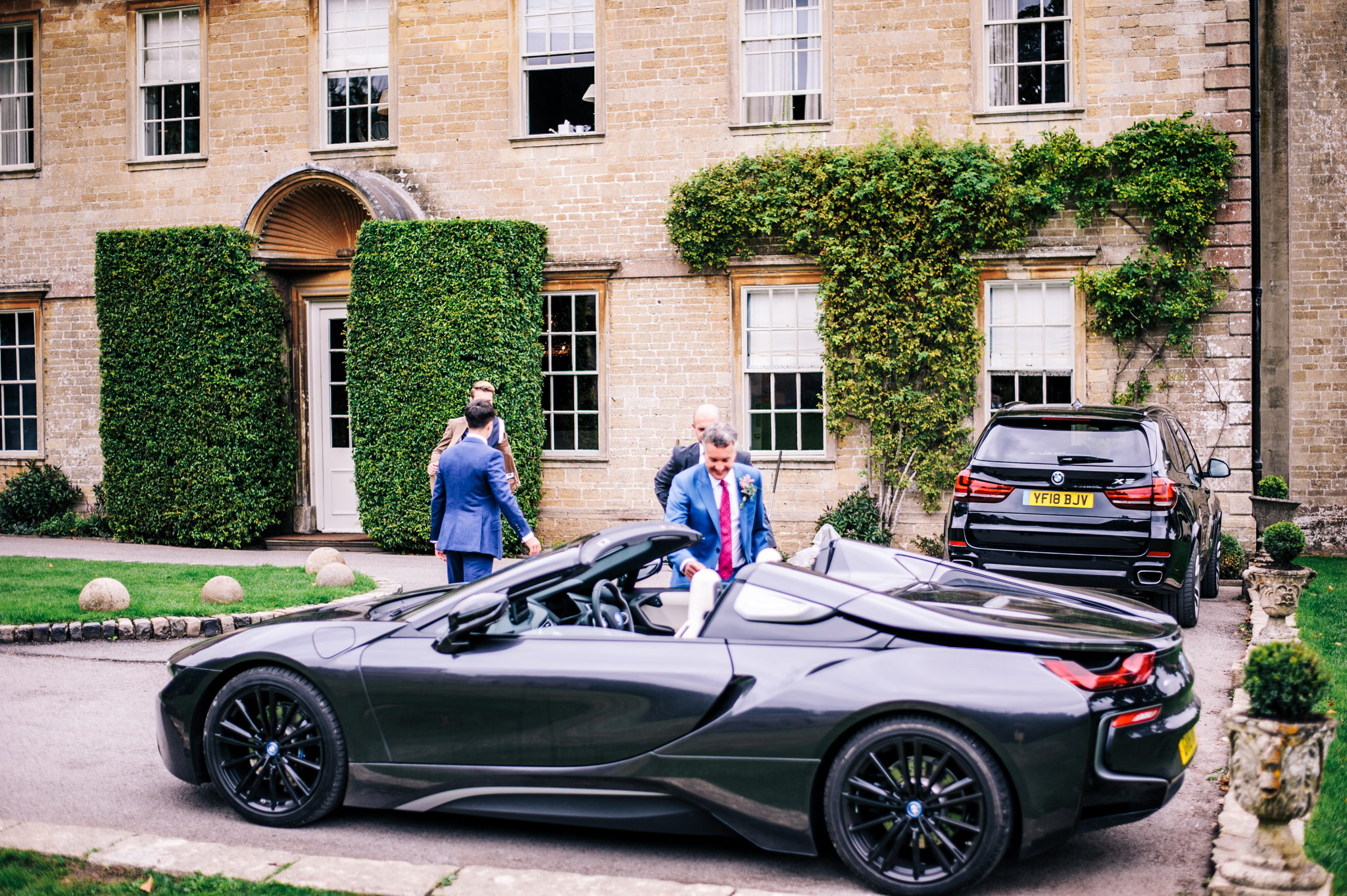 Groom and best man laughing next to sports car at Babbington House