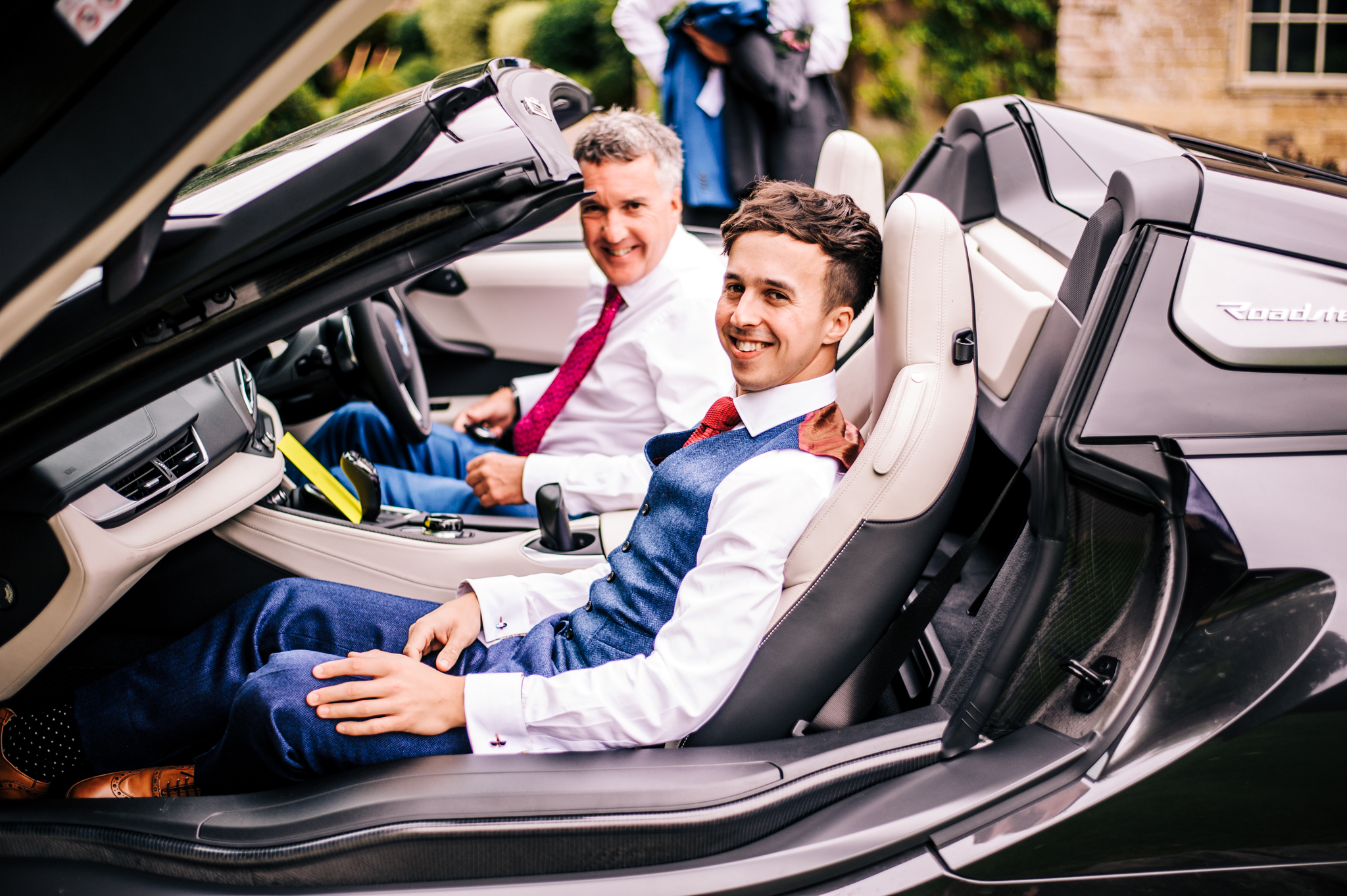 Groom sat in sports car at Babbington House about to leave for Wedding near Mells