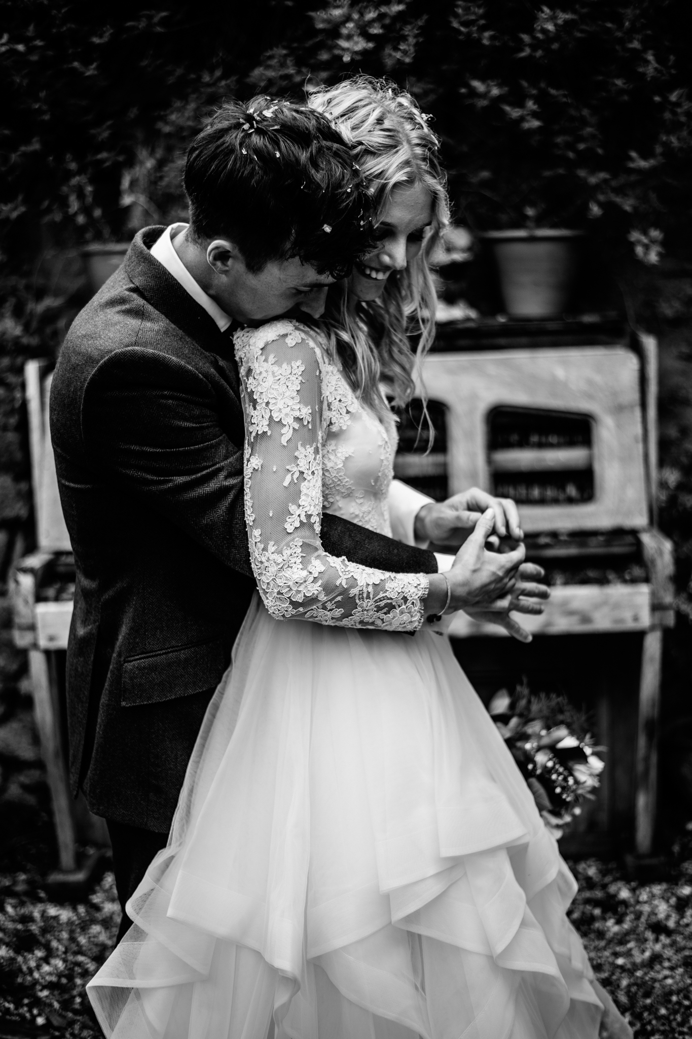 black and white portrait of glamorous couple next to weather piano outside at Mells walled garden