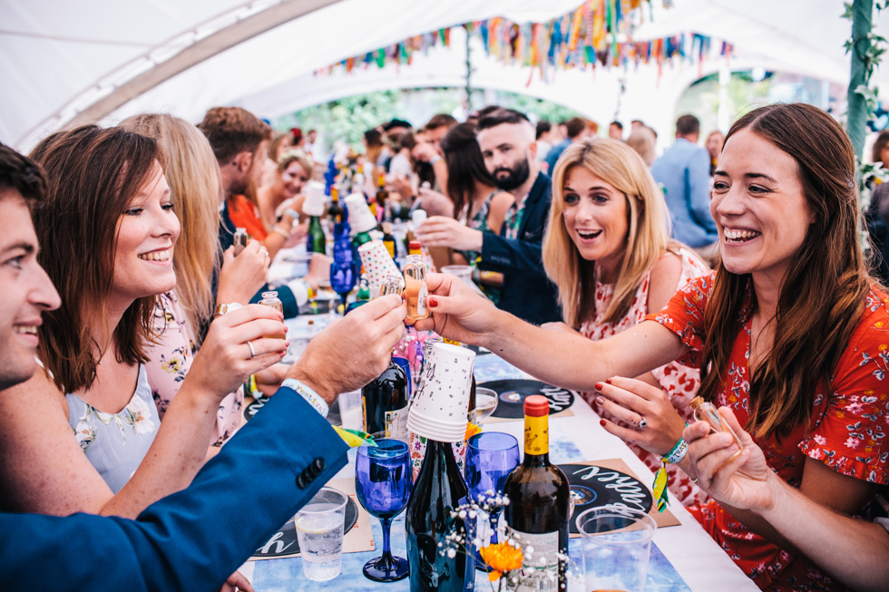 guests doing shots of home made alcohol at festival wedding