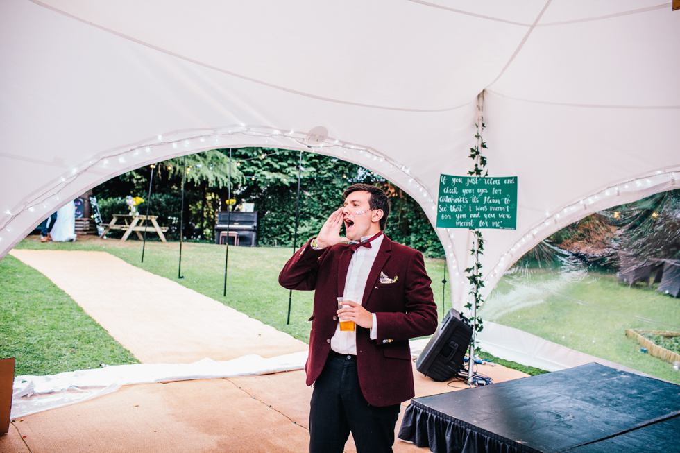 brides brother announcing bride and groom into wedding tent