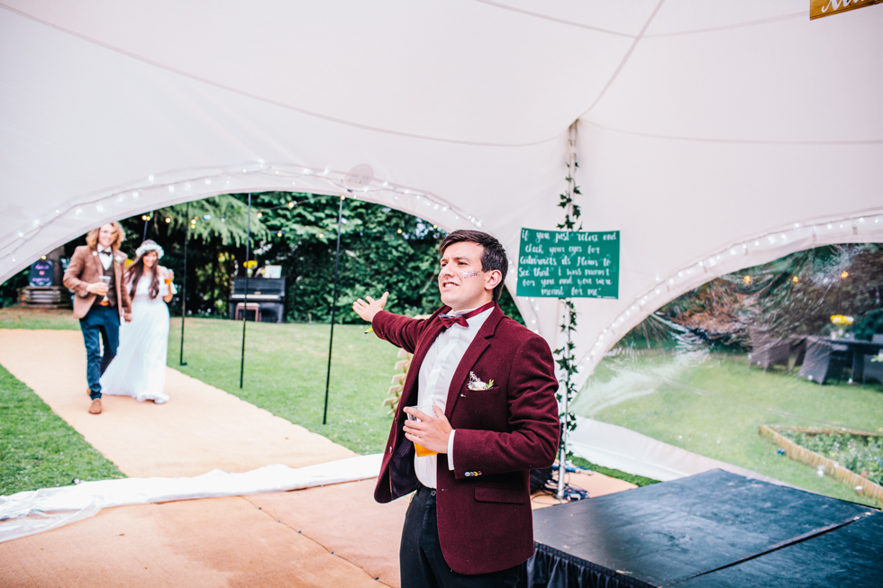 brides brother announcing bride and groom into wedding tent dressing in dinner suit with bow tie