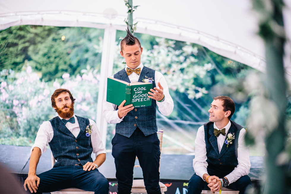 grooms best men with mohawk reading from a book with the title cool and good speech on the front