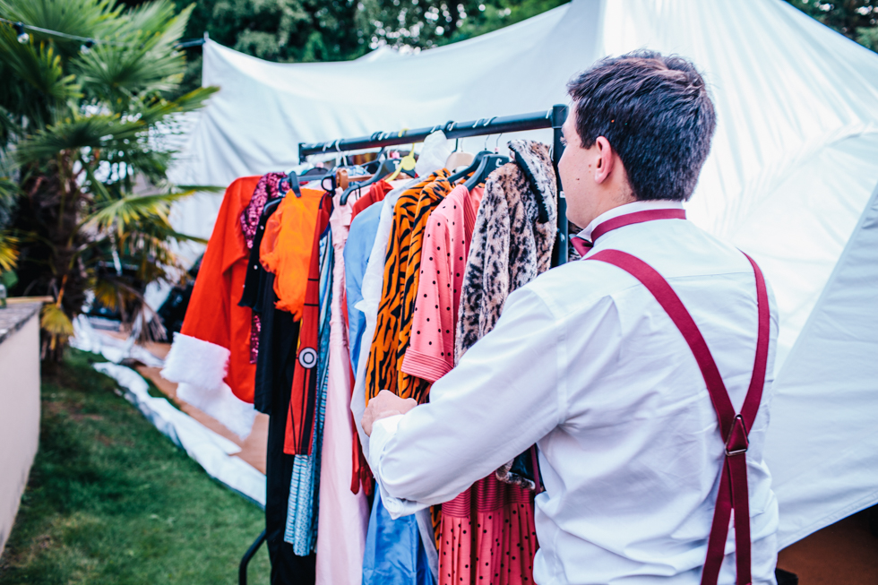 brides dad carrying dress up clothes on rack for guests