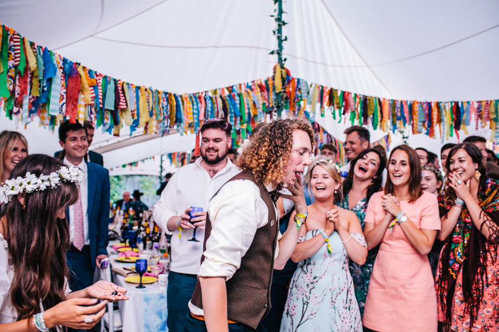 bride shoving cake into grooms face in food fight at festival wedding