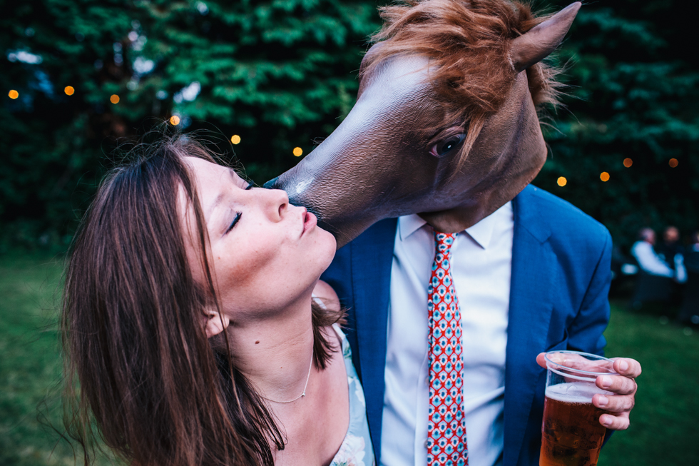 wedding guest being kissed by horse mask at festival wedding