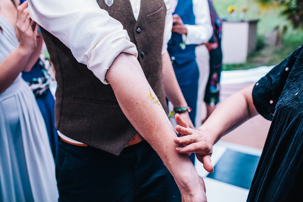 temporary tattoos being stuck on wedding guest arm at festival wedding