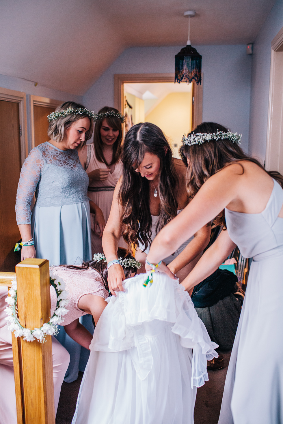 bride laughing with bridesmaids whilst putting wedding dress on