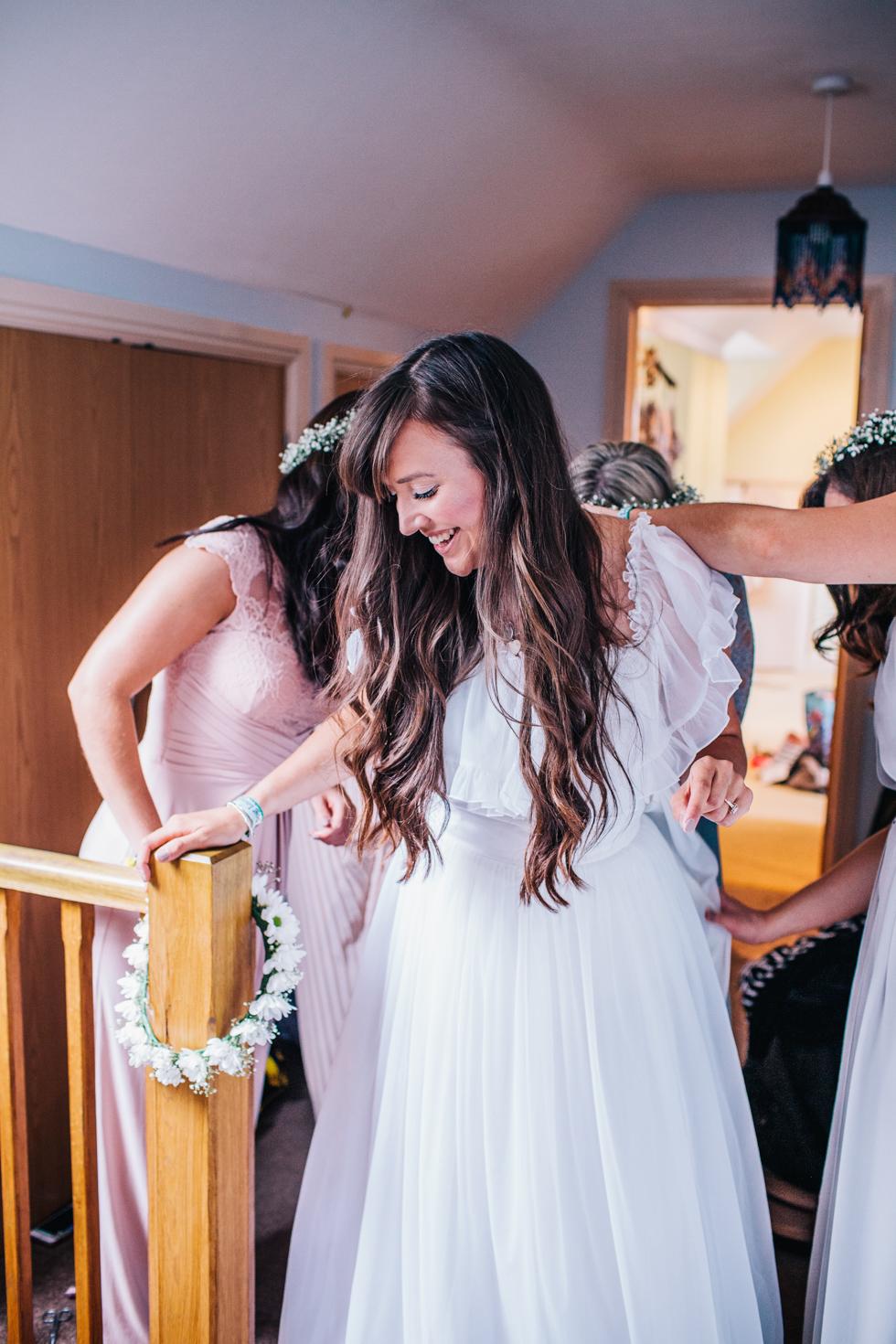 bridesmaids helping bride to fasten wedding dress