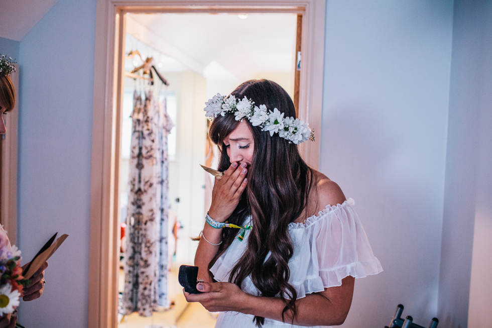 bride opening gift from groom on morning of wedding wearing flower crown and charity shop wedding dress