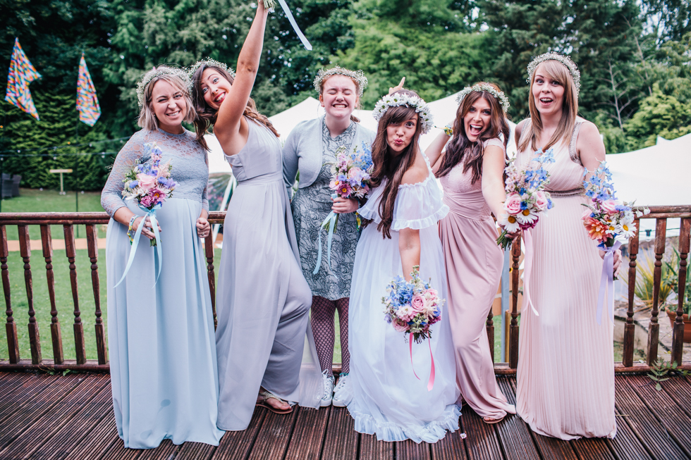 bride and bridesmaids with hands up in the air group shot