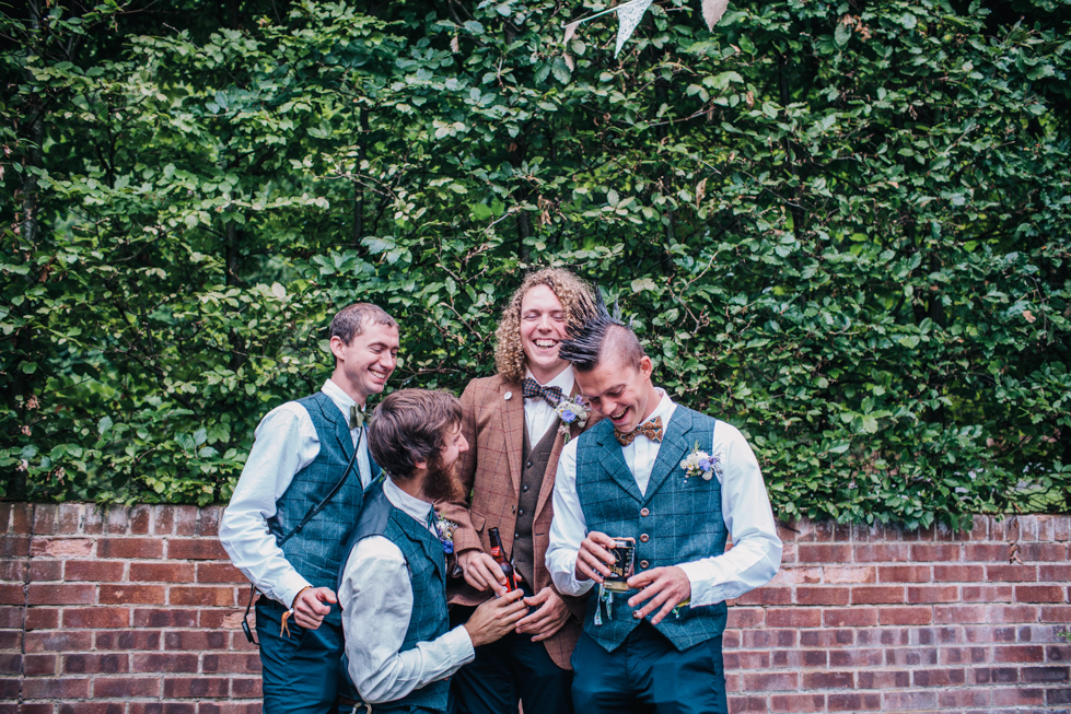 boys messing about in group shot at festival wedding wearing tweed