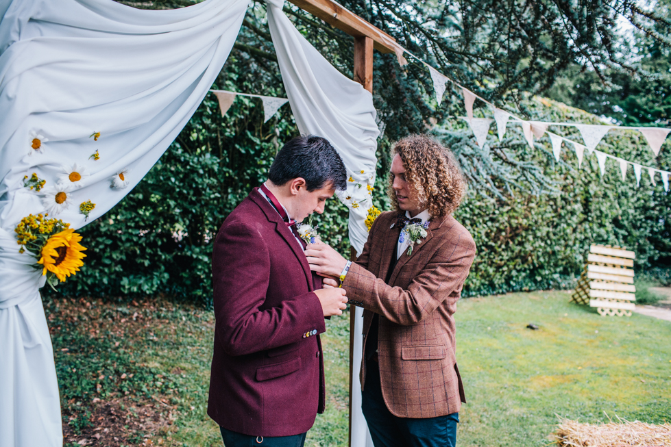 groom straightening brother in laws button hole at outdoor festival wedding