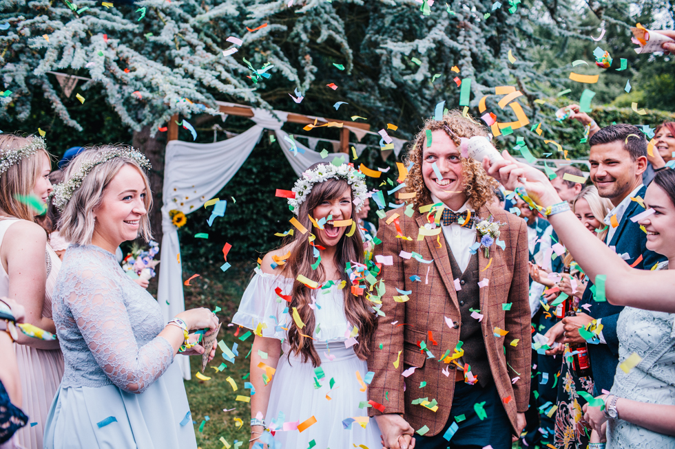 bright confetti being throw at outdoor wedding ceremony