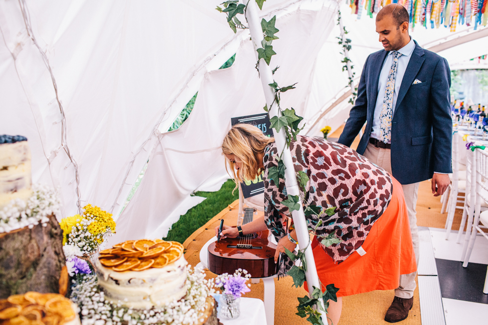 guests signing guitar at wedding instead of wedding guest book
