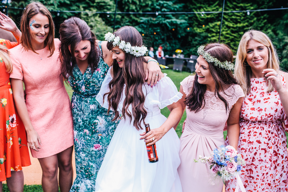 bride hanging with her girlfriends outside at festival wedding