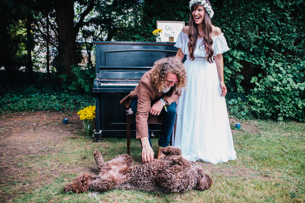 bride and groom with their dog in group shot taken outside in front of old piano