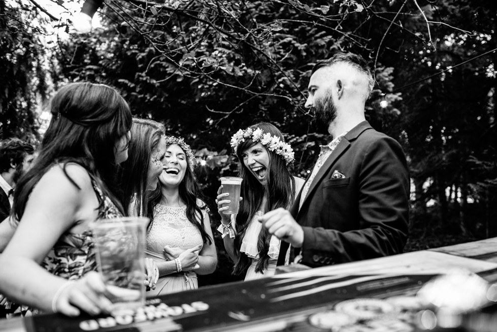 bride laughing at bar with wedding guests