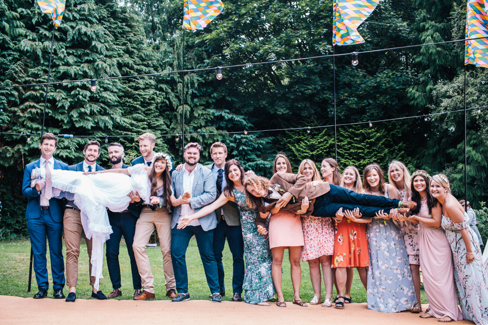large group shot of friends lifting bride and groom at festival outdoor wedding