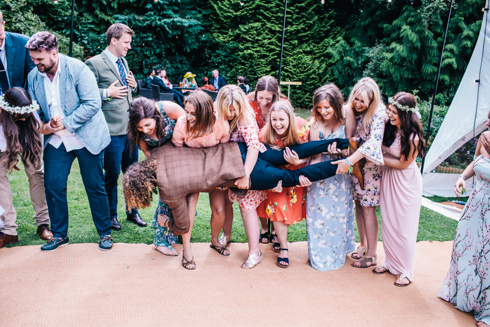large group of friends dropping groom after group shot outside
