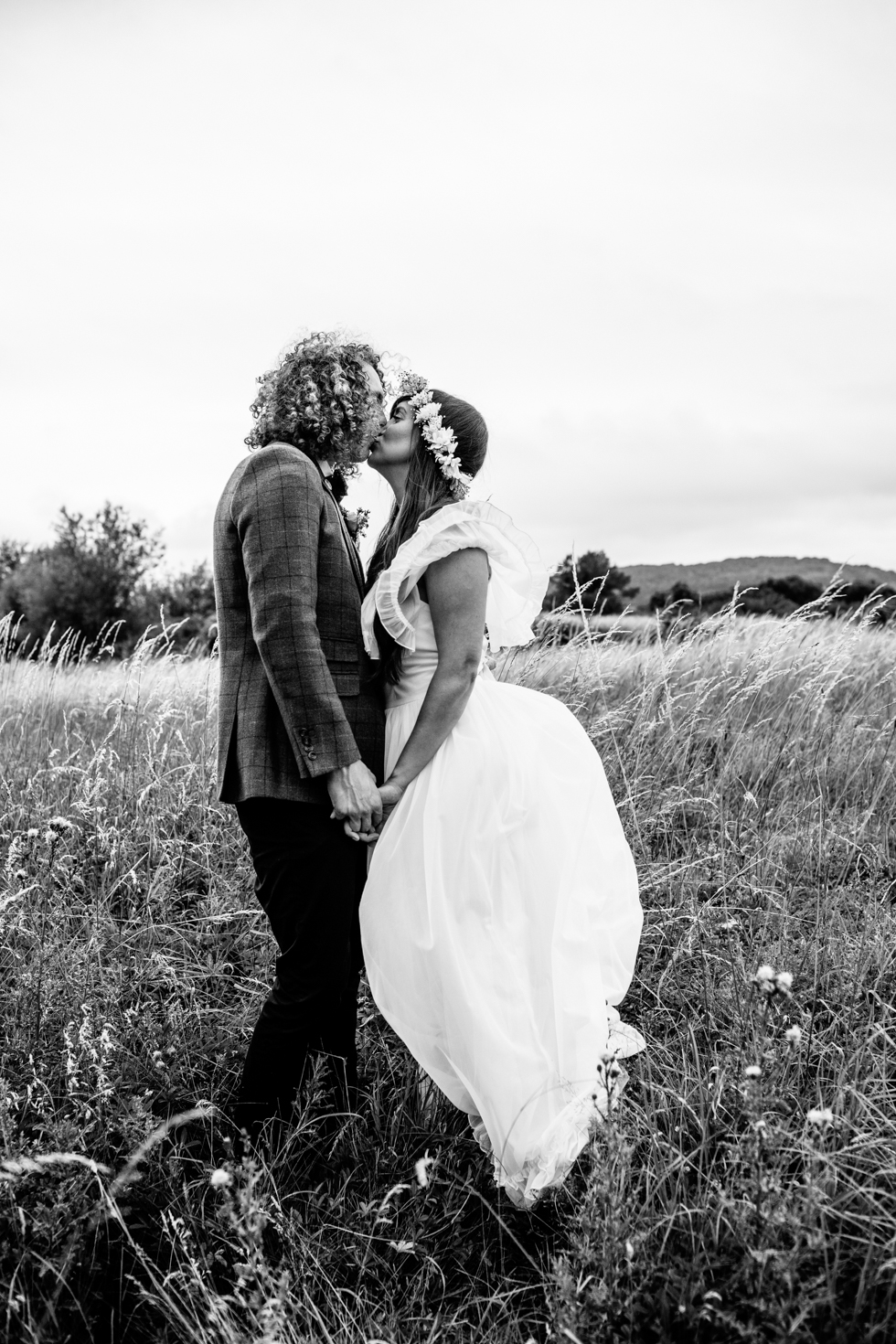 couple portrait of bohemian bride and long haired groom walking through fields at festival wedding