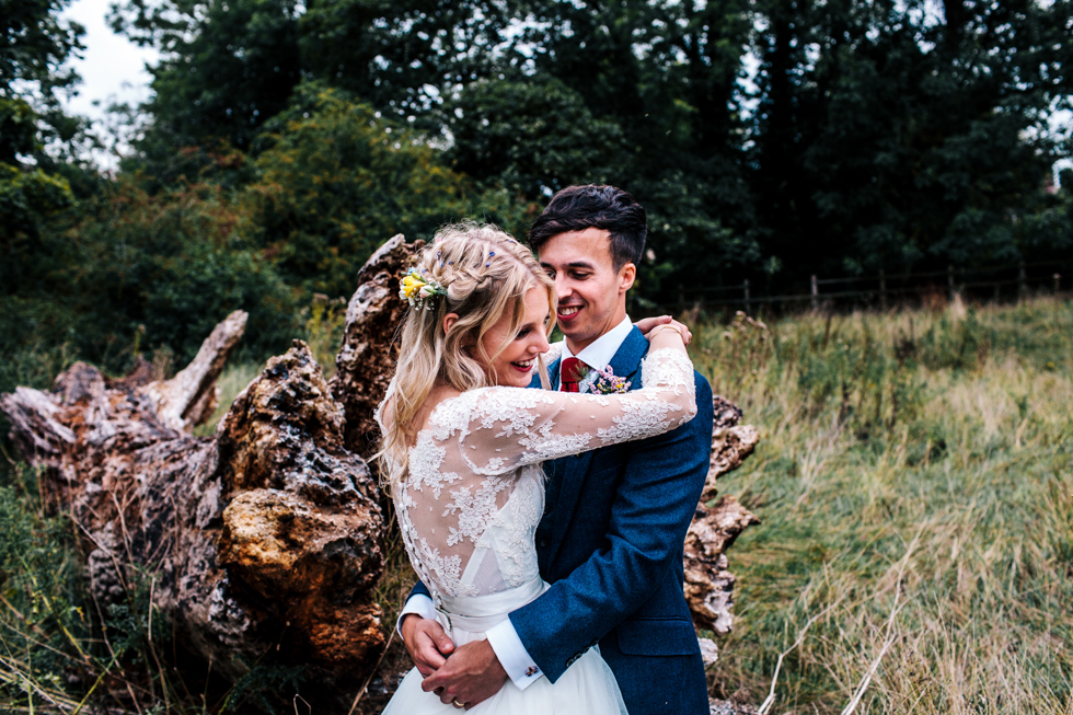 bride in lace Emma Tindley separate top and groom in navy blue and red tie three piece suit snuggled together for couple portrait at wedding in Mells walled garden