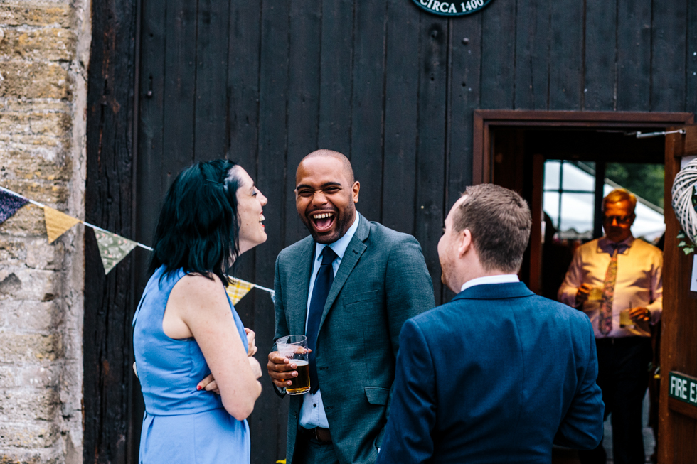 guests laughing outside at evening wedding reception with home-made cocktails