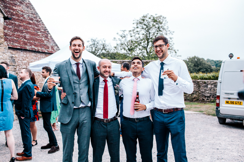 two really tall guys and two short guys standing next to each other for comparison at wedding