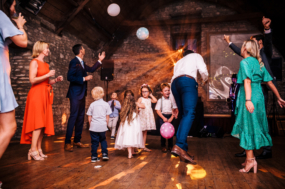 young kids playing with balloons at wedding reception