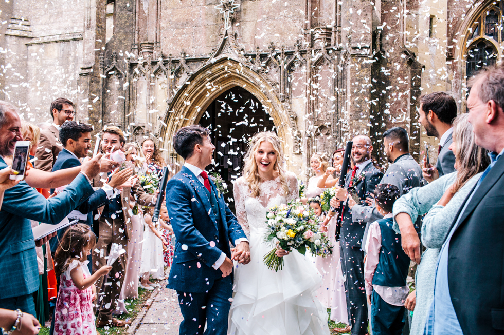 Confetti cannon being launched outside church to create epic photograph with loads of white confetti