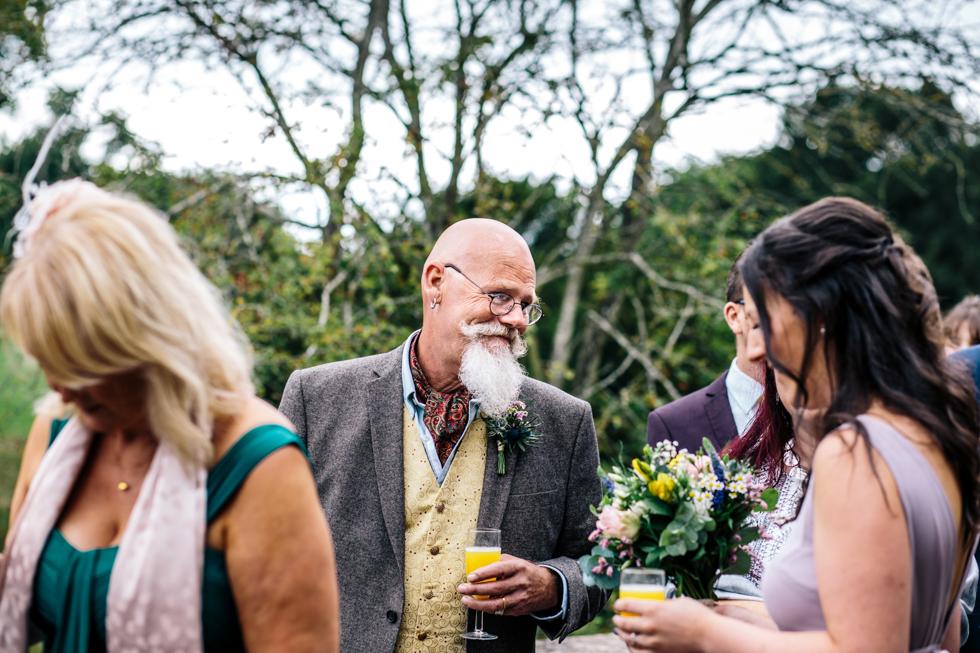 brides bohemian dad chatting at wedding reception