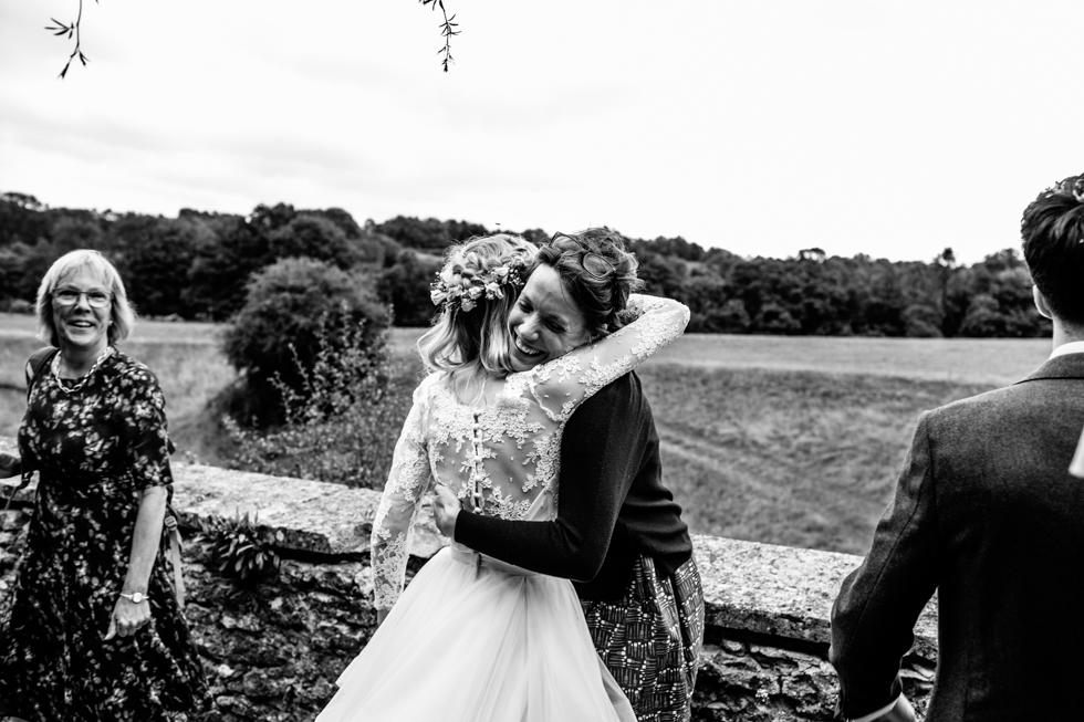 bride greeting wedding guest with huge hug