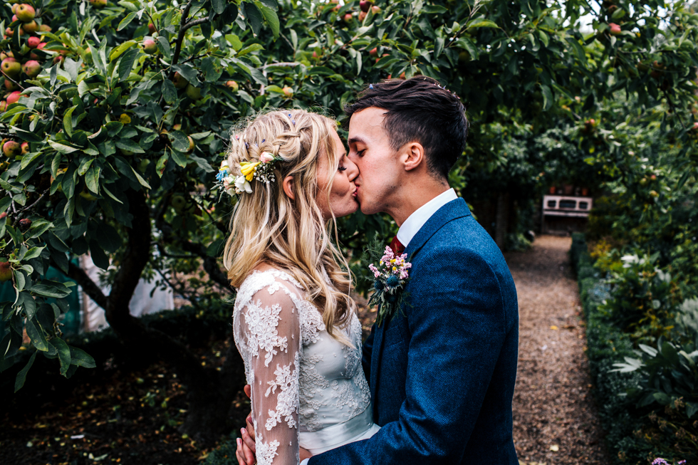 bride and groom kissing under apple orchard at Mells walled garden