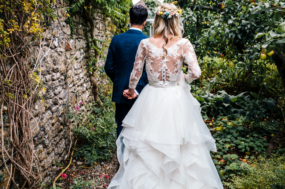 bride wearing Emma Tindley lace top and layered skirt walking through apple orchard at Mells walled garden