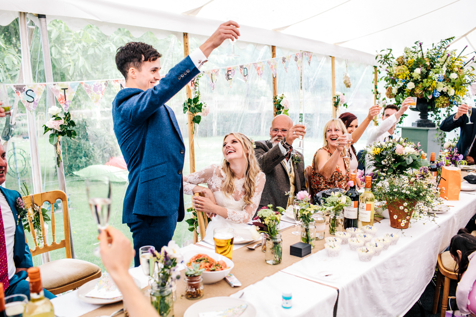 groom raising his glass to his wedding guests during speeches