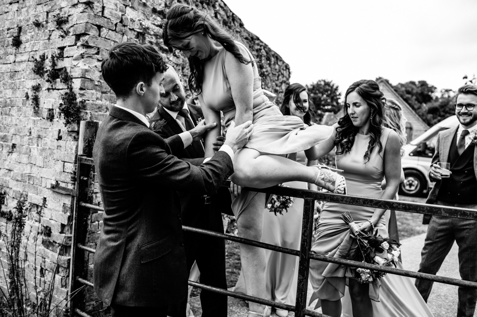 groom carrying bride over fence at wall garden Mells