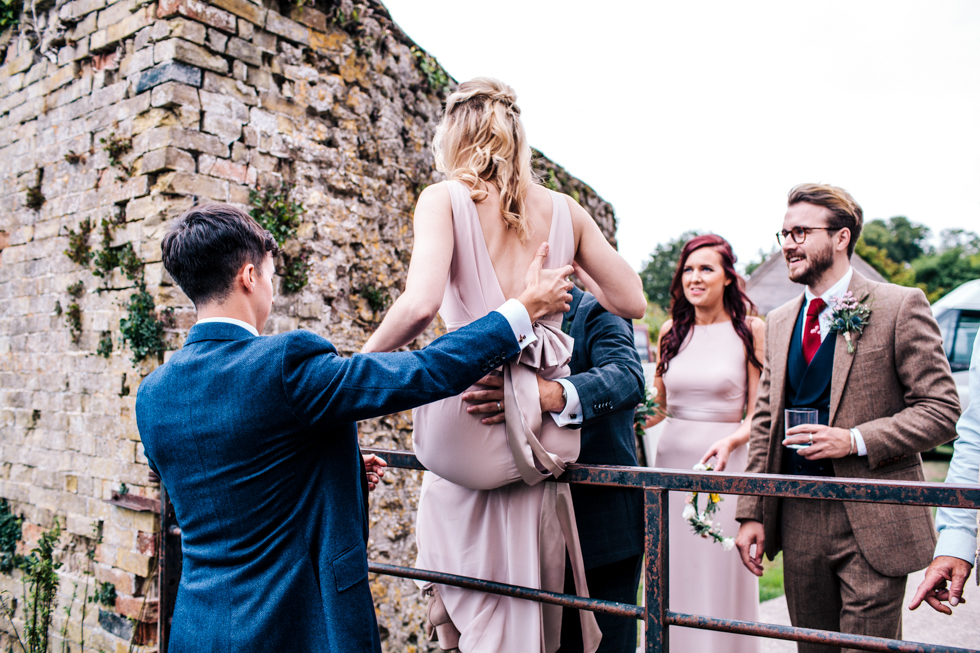 bridesmaid being carried by groom over fence for group shots