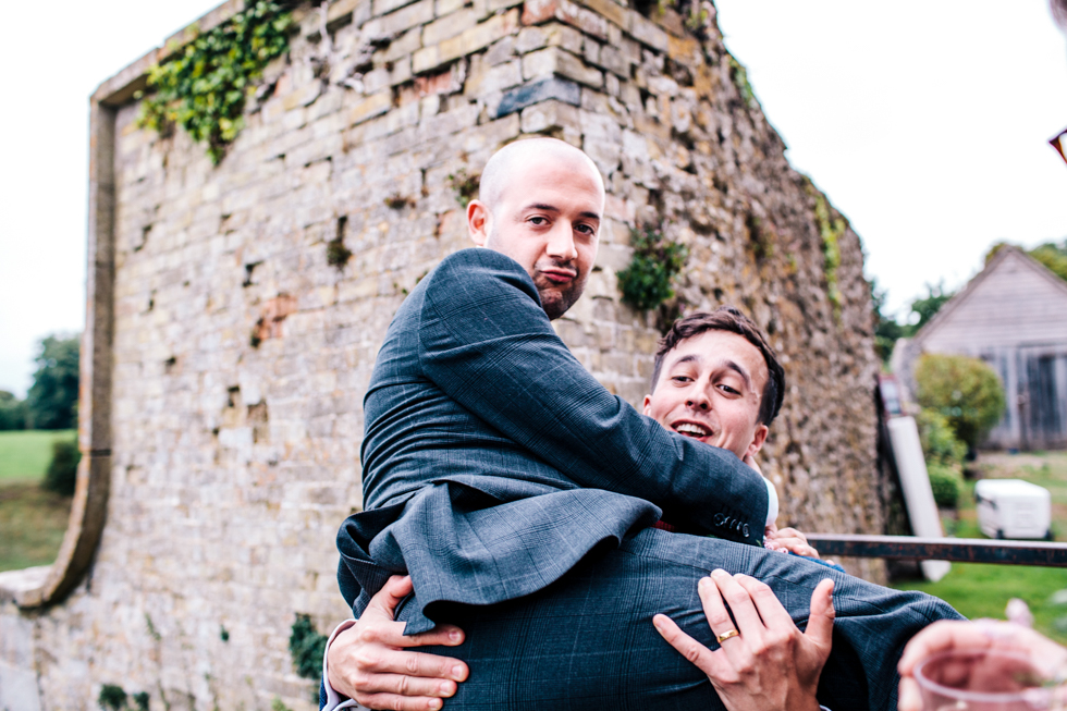 best man being carried by groom over fence