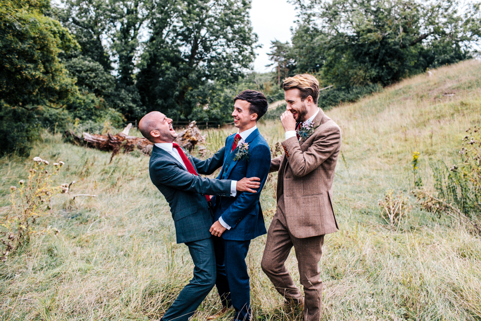 groom best man and usher laughing and messing about in a field for their own special photo at wedding near Mells frome