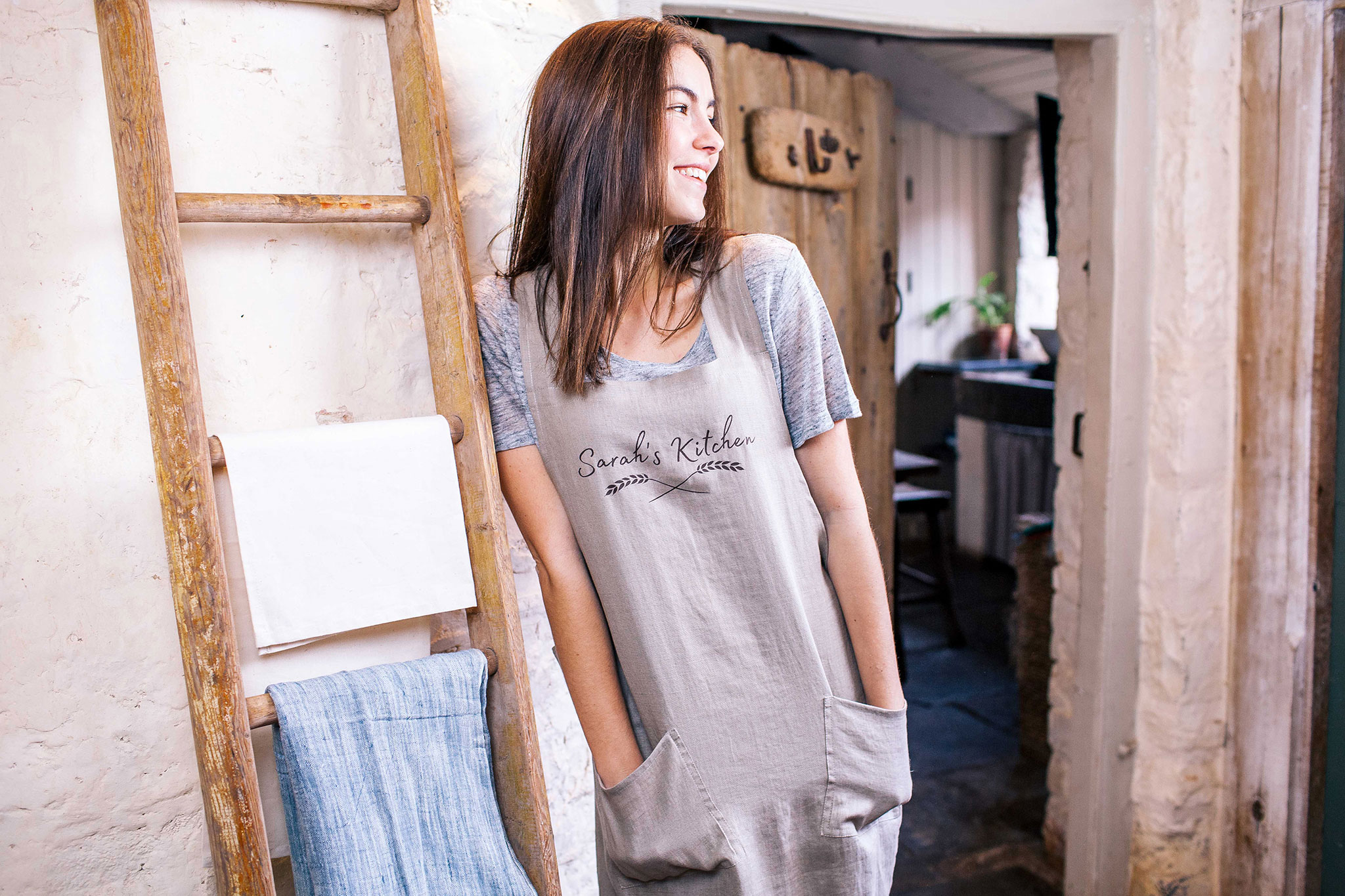 brunette woman standing in cotton hand printed apron